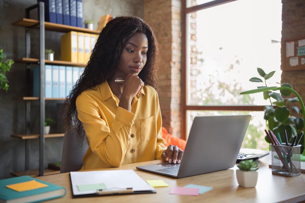 Mulher negra com a mão no queixo trabalhando, sentada em frente ao seu notebook